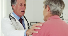 Happy senior doctor talking to elderly patient with hand on shoulder Stock Footage