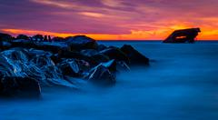 long exposure at sunset of the uss atlantis shipwreck at a jetty after-sunset - stock photo