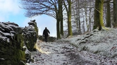 woman hiking up a snow covered mountain trail - stock footage