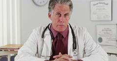 Senior doctor talking to camera Stock Footage
