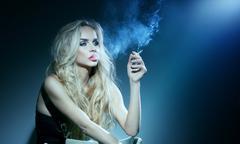 Elegant blonde woman smoking a cigarette. Stock Photos