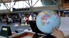 Woman checking globe map at information desk inside yvr airport Stock Footage