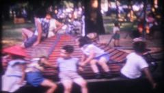1416 - children play on vintage rides at the park - vintage film home movie - stock footage