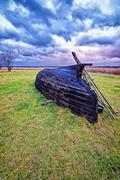 Overthrown fisherman boat on the lake shore at stormy weather Stock Photos