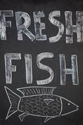 A Handwritten sign promoting fresh fish Stock Photos