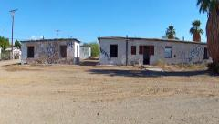 Driving By Abandoned Dilapidated Apartments In Small Desert Town - stock footage