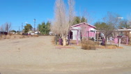 Stock Video Footage of Driving By Small Homes In Dusty Desert Town- Niland CA