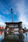 Docking oil rig at the Gdansk Shipyard under construction with fisher man in Gda Stock Photos