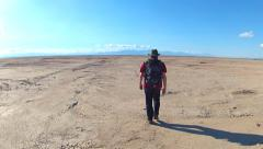 Man Hikes Away From Camera Across Dried Lake Bed Desert Stock Footage