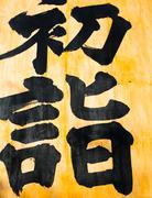 Japanese calligraphy, black letters on a yellow background - stock photo