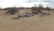 Stock Video Footage of Piles Of Trash Left By Desert Squatters Zoom- Niland CA