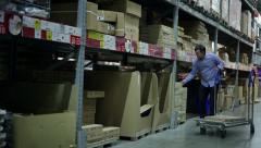 Warehouse, man takes a box Stock Footage