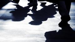 silhouette of waling people. shadows of walkers crossing street - stock footage