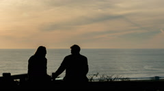 Silhouette of Friends Hanging out Watching Sunset Beach Beautiful Scenic Ocean Stock Footage