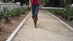 Female Walking in Park with Camera Panning Stock Footage