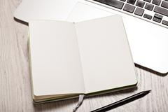 Open notepad with blank pages on white table with laptop Stock Photos