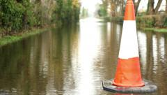 Pan on Traffic cone at flooded road, warning sign for inundated street Stock Footage