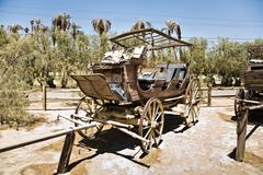 Old wagon and coaches at the entrance of the furnance creek ranch in the midd Stock Photos