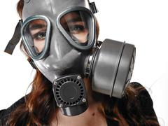 young adult woman and gas mask - stock photo