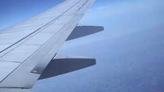 Airplane wing flying, during flight, blue sky aerial shot - stock footage