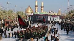 Shrine's servants walks to Imam Hussein's shrine, al-Abbas shrine in back 769 Stock Footage