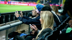 Soccer fans filming the football match Stock Footage