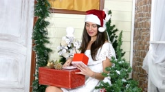 Girl poses on a house porch in studio with gift box. Christmas theme - stock footage