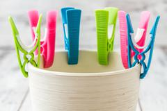 modern plastic green, blue, pink clothes pin lined on white ceramic pot - stock photo