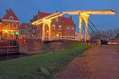 Stock Photo of medieval bridge and houses in the village enkhuizen the netherlands by twilig
