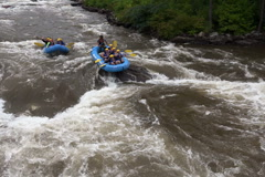 White water rafters hung up on rock in rapids - stock footage