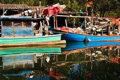 Huts and colorful  fisherboats at the mangrove everglades in a small fisherma Stock Photos