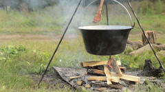Cooking stew at the camp Stock Footage