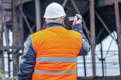 Stock Photo of Building inspector filmed with camcorder in factory