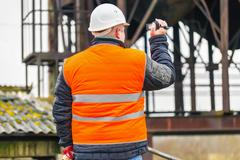 Building inspector filmed with camcorder - stock photo