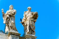 statues at the top of basilica of saint john lateran in rome, italy. - stock photo