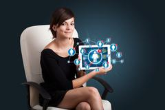Stock Photo of young woman holding tablet with social network icons