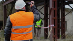 Building inspector with camcorder and with worker in background Stock Footage