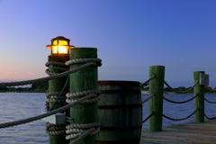 Lamps illuminate boardwalk around lake at dusk - stock footage