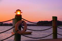 Lamps illuminate boardwalk around lake at sunset - stock footage