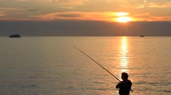 Silhouette of a fisherman reeling in fish catch Stock Footage