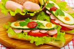 big appetizing fast food baguette sandwich with lettuce, tomato and frankfurt - stock photo