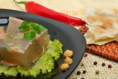 delicious fish mackerel aspic on white plate with mustard and green salad - stock photo