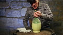 Elderly man cleaning a dusty wine bottle Stock Footage