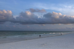Walkers on Clearwater beach at sunrise Stock Footage