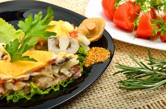 baked meat stuffed with onion, mushrooms, cheese, parsley on black plate, tom - stock photo