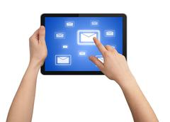 a male hand holding a touchpad pc, one finger touches e-mail sym - stock photo
