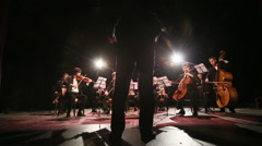Conductor conducting an orchestra - stock footage