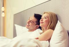 Happy couple dreaming in bed Stock Photos