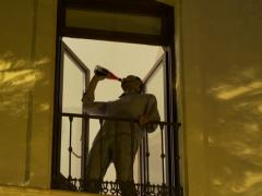 Drunk young man drinking red wine from bottle on balcony at night NTSC Stock Footage