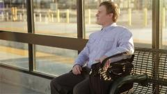 Male Commuter sits down at a bench waiting for the bus Stock Footage